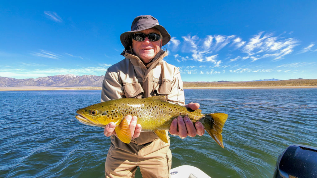 A fly fisherman experiencing some of the best trout fishing in Mammoth and holding a brown trout while on a boat on Crowley Lake with a blue sky above with wispy clouds.