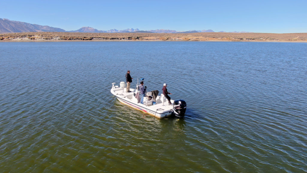 A center console bay boat anchored in the middle of Crowley Lake with 3 fishermen experiencing some of the best trout fishing in Mammoth.A fly fisherman
