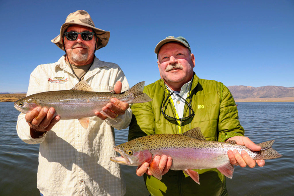 Two fly fishermen experiencing some of the best trout fishing in Mammoth and holding a pair of colorful rainbow trout on Crowley Lake.