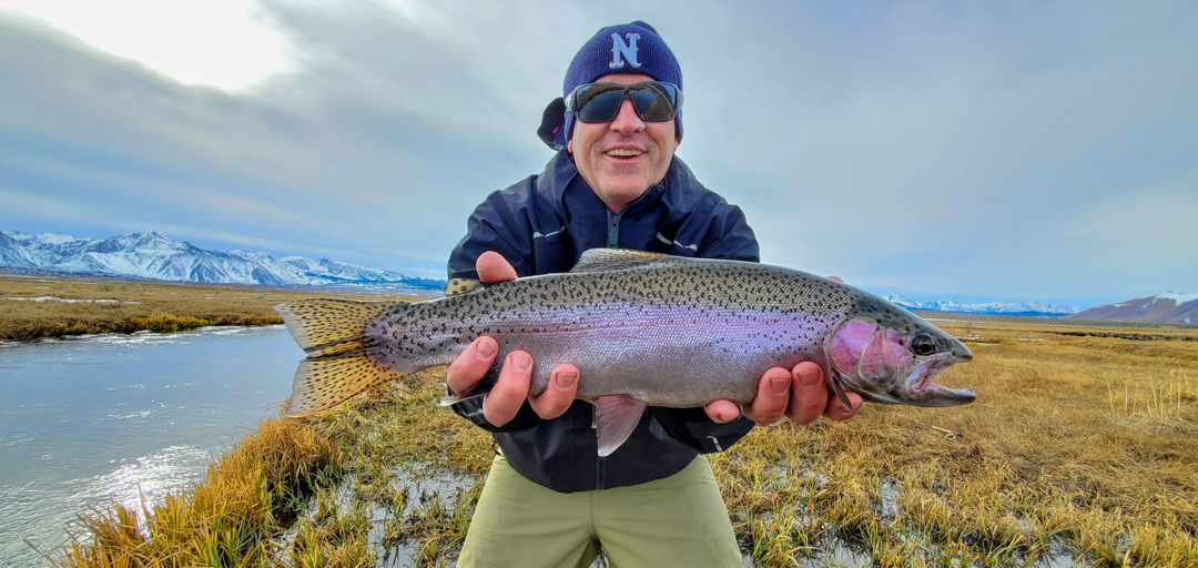 A fly fisherman holding a larger rainbow trout in the winter on the Upper Owens River.