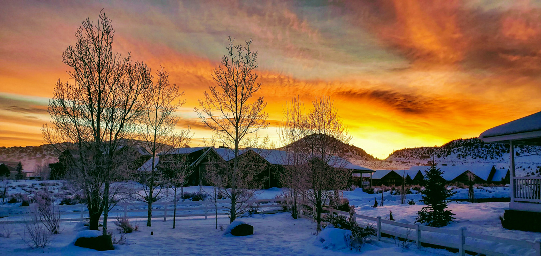 An orange colored sky glows from a winter morning sunrise in Crowley Lake with freshly fallen snow on the ground.