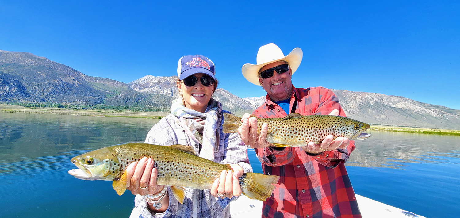 A husband and wife holding a pair of brown trout from Crowley Lake while fishing with an Eastern Sierra Fishing Guide with a view of Mammoth Mountain in the background.