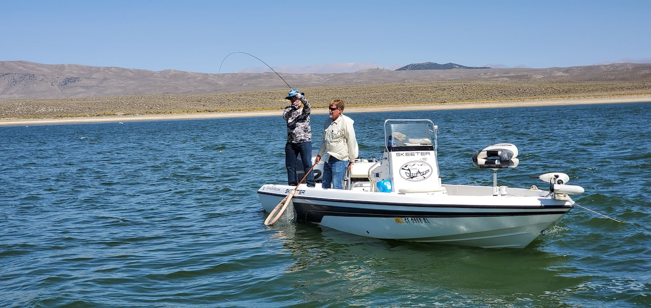 Sierra Drifters Guide Jerry Gilpin assists a fly fisherman in landing a trout from Crowley Lake on a boat.