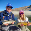 A fly fisherman and his daughter holding brown trout from Crowley Lake with fly fishing hats in blue and pink.