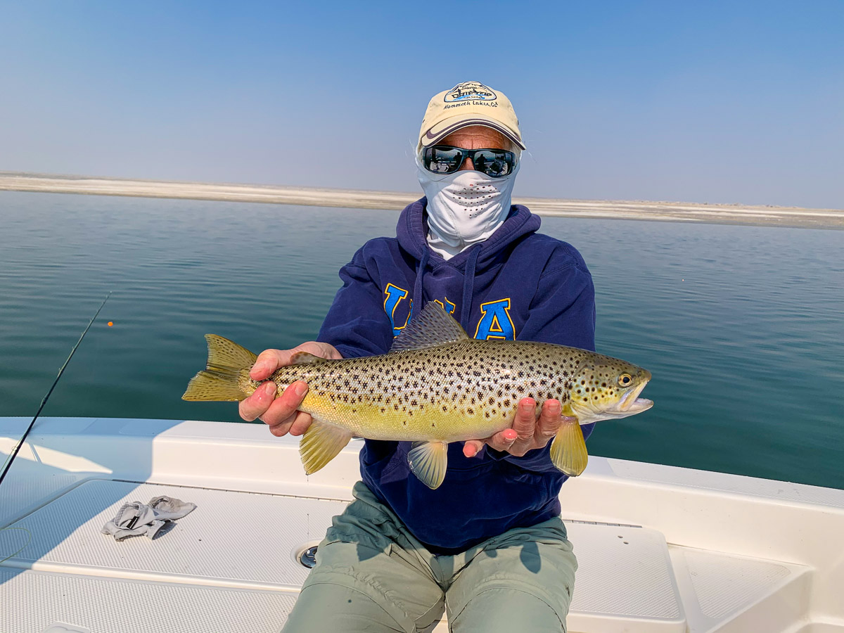 A lady angler wearing a sun gaiter displays a healthy brown trout from Crowley Lake