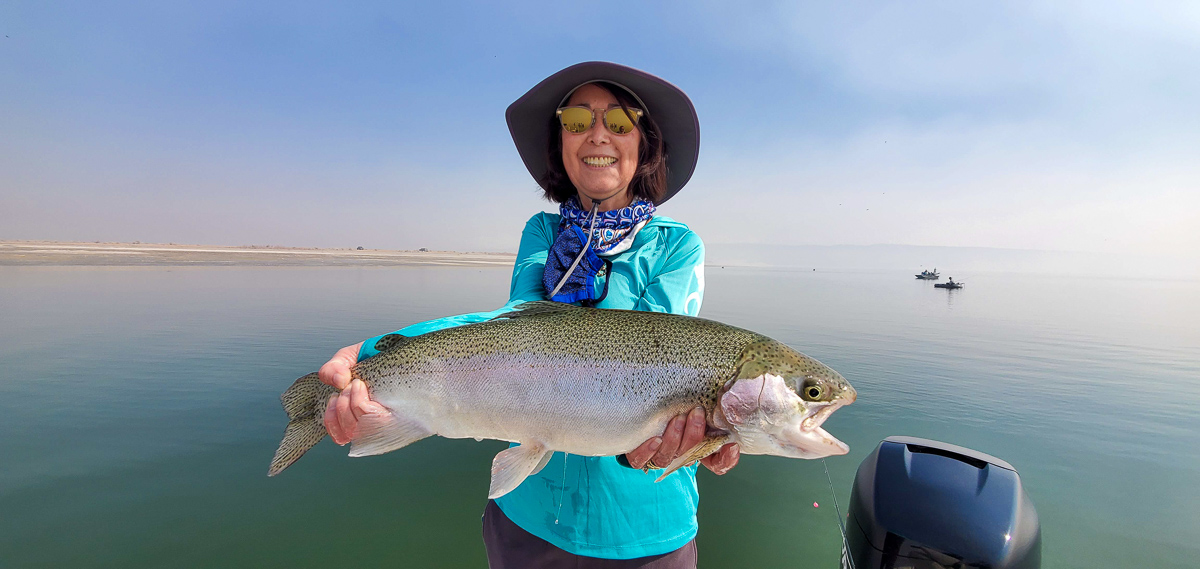 A lady angler dispays an enormous rainbow trout from Crowley Lake with Sierra Drifters Guide Service.