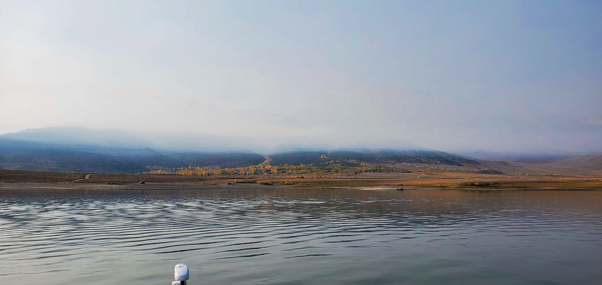 A view of Crowley Lake in the fall showing aspens in fall colors and a veil of smoke from a nearby wildfire.