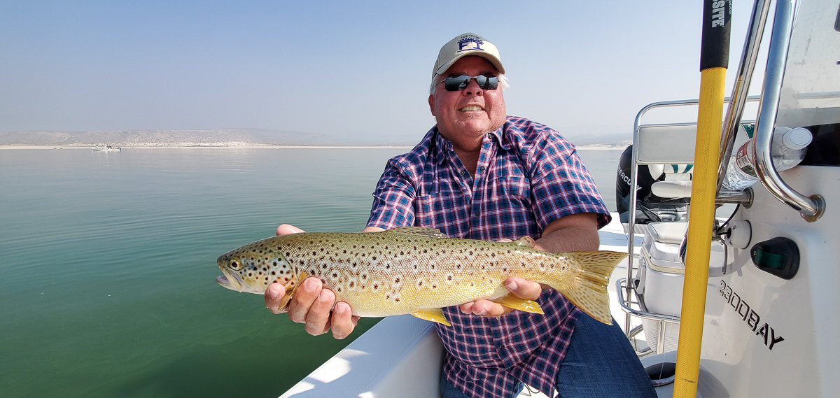 A smiling angler holding a brown trout from Crowley Lake.