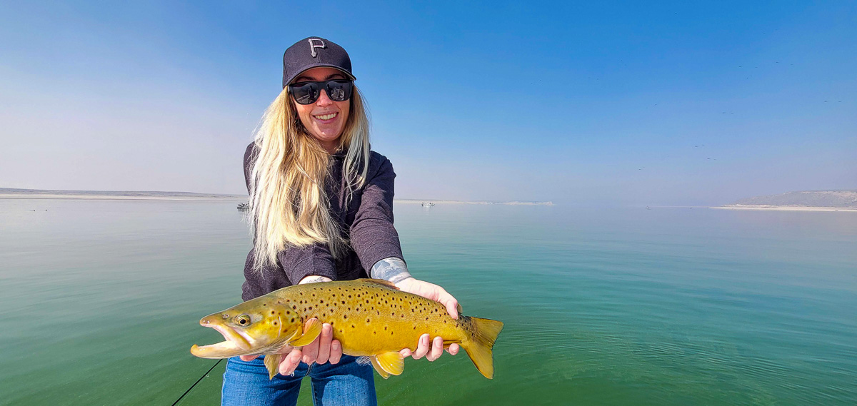 A female angler holding a very golden colored brown trout from Crowley Lake.