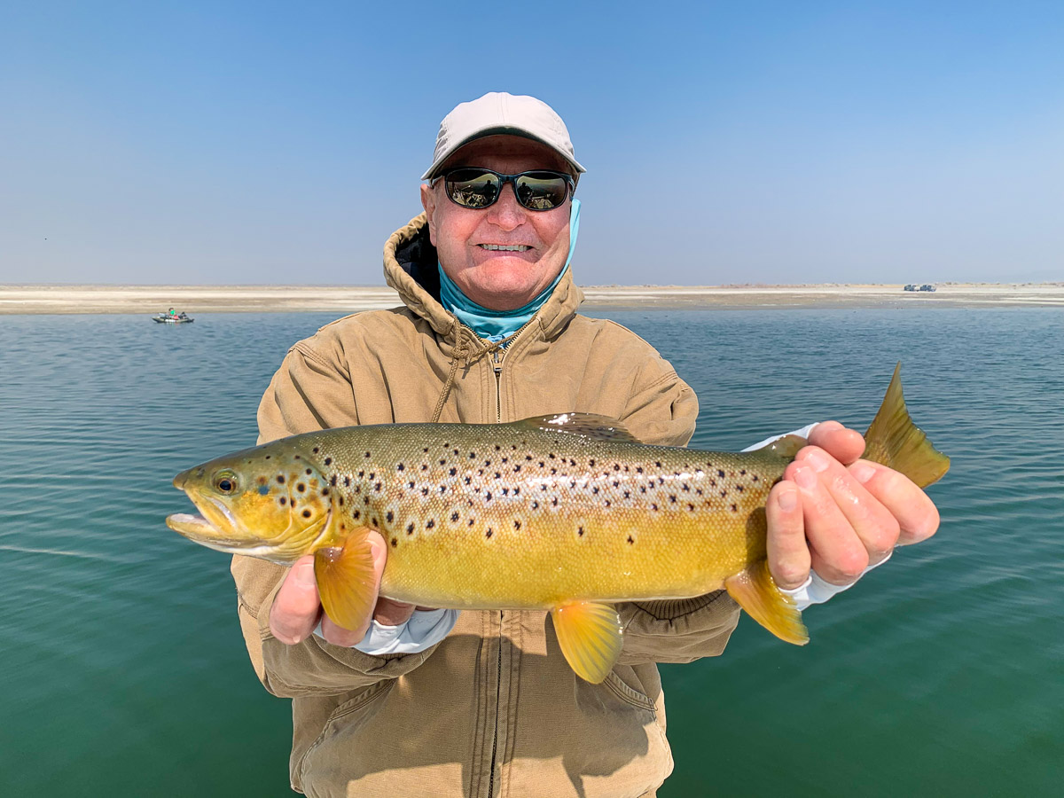 A smiling angler holding a brown trout in fall spawning colors from Crowley Lake.