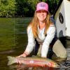 A lady angler kneeling in a river holding a steelhead trout and wearing a pink baseball hat.