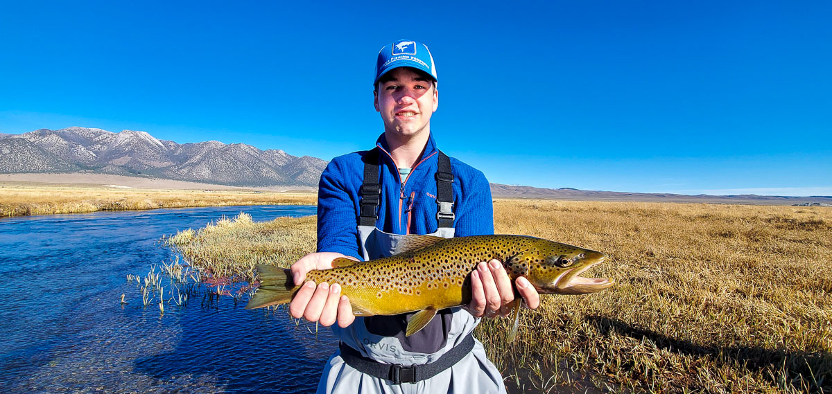 A fly fisherman holding a large brown trout in spawning colors in the fall while standing in the Upper Owens River.
