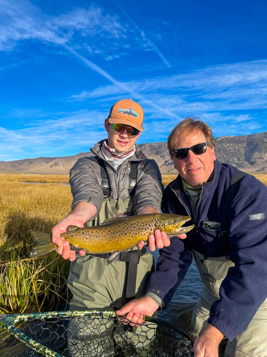 A young fly fisherman holds a brown trout in spawning colors in the fall from the Upper Owens River while his dad assists holding the net.
