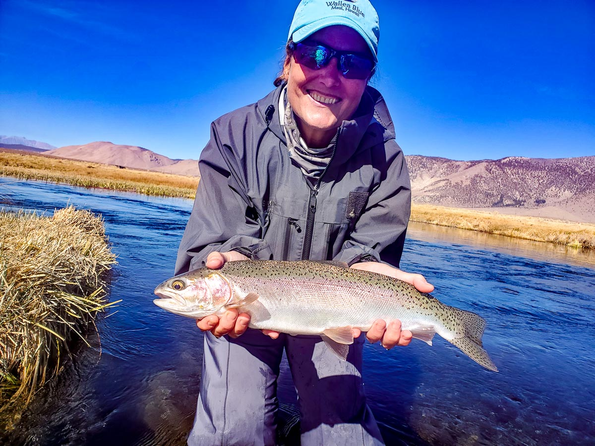 A fly fisherwoman dispays a large rainbow trout while standing in the Upper Owens River.