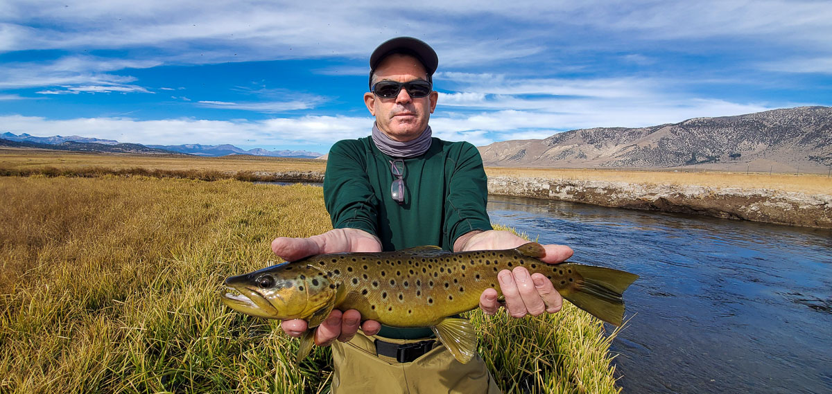 A fly fisherman holding a brown trout from the Upper Owens River in early November.