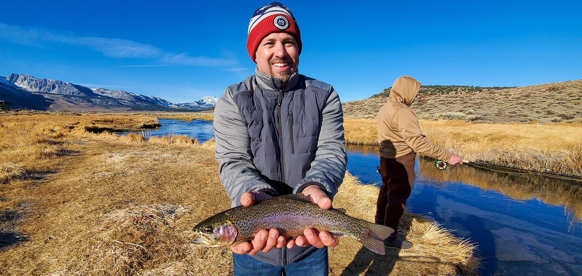 A fly fisherman with a red beanie holding a rainbow trout from Hot Creek in the Eastern Sierra.