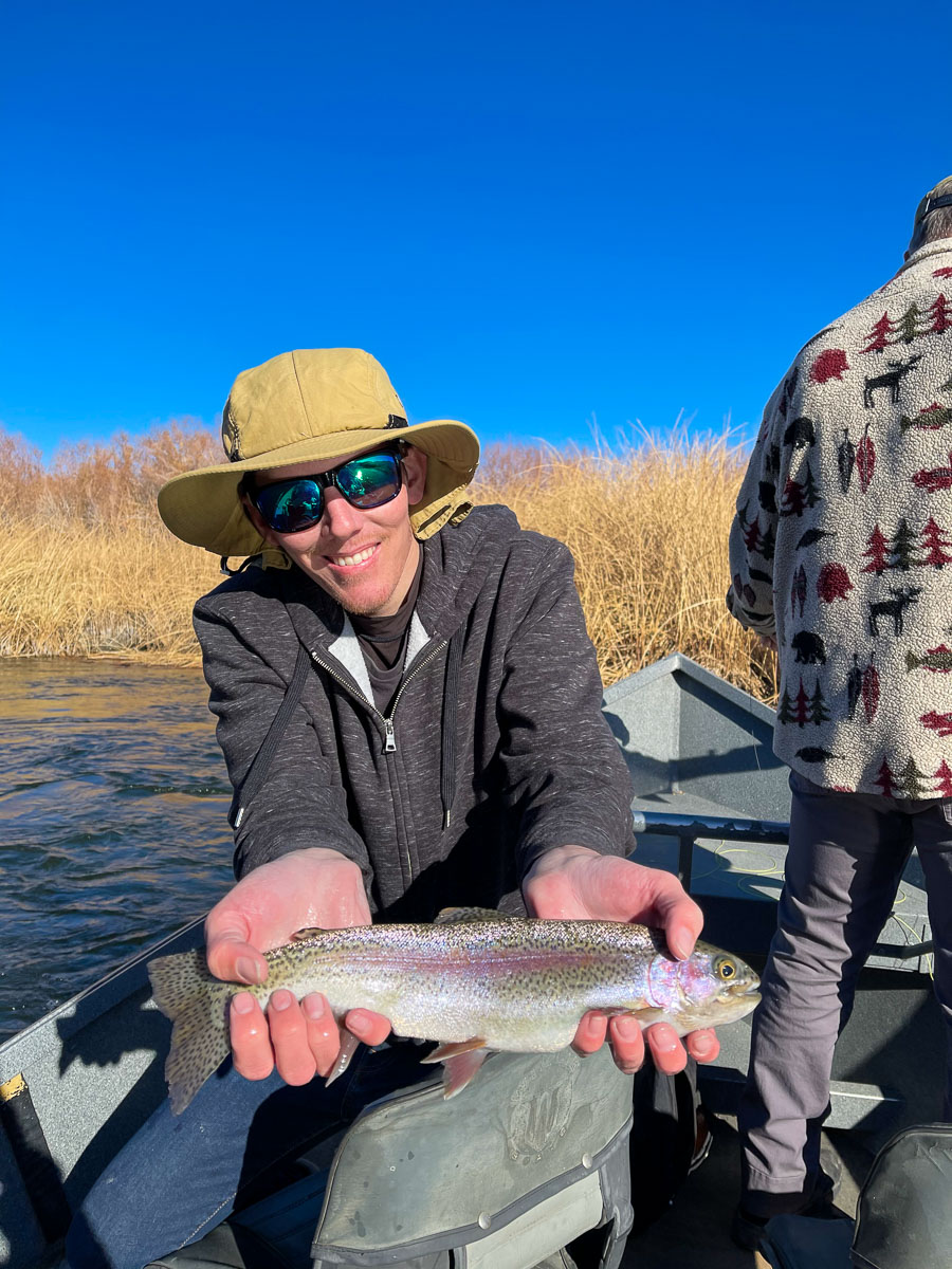 A fisherman holding a rainbow trout in a drift boat from the Lower Owens River.
