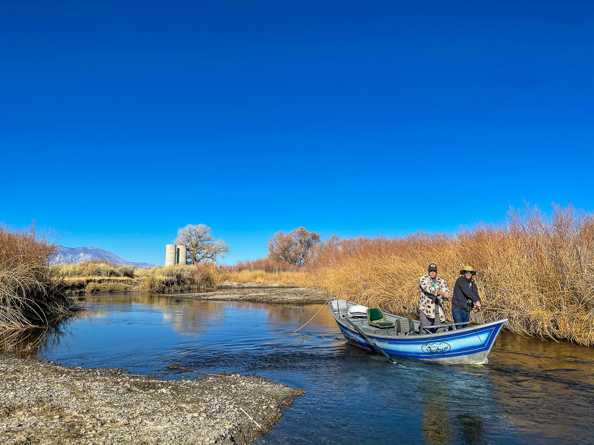 A couple of fly fisherman fishing on the Lower Owens River from a blue drift boat.