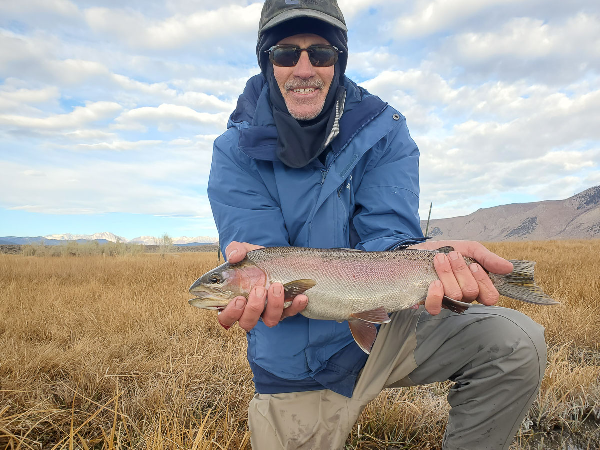 A young fly fisherman holding a rainbow trout during the fall spawn from the Upper Owens River.
