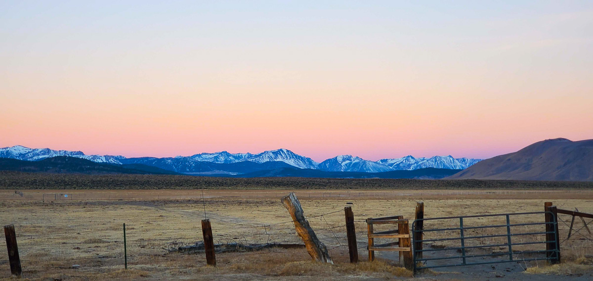A cold morning before sunrise on the Upper Owens River with a cattle fence in the foreground and snowcapped mountains in the background.