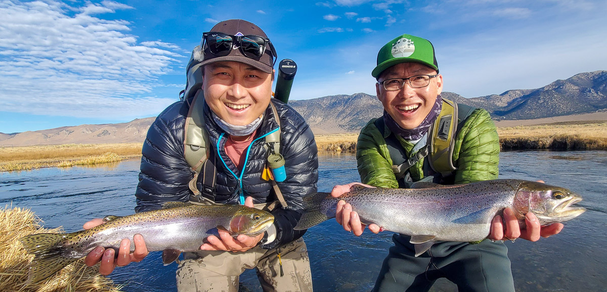 A couple of fly fisherman holding giant rainbow trout from the Upper Owens River.