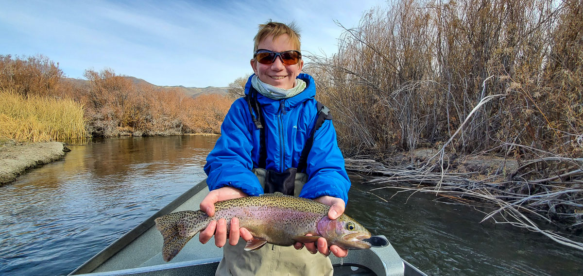 A young fly fisherman fishing on the Lower Owens River from a drift boat and holding a rainbow trout.