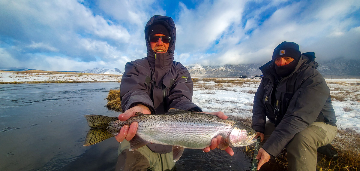 A fly fisherman holding a rainbow trout in spawning colors from the Upper Owens River in the snow.
