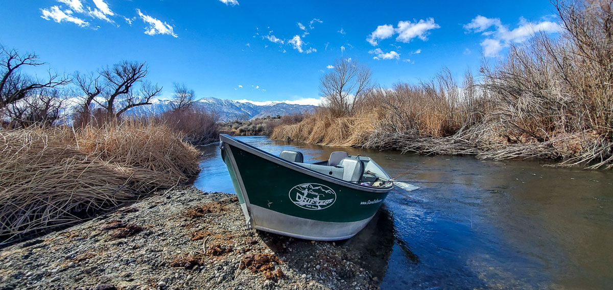 A drift boat resting on a river bank on the Lower Owens River.