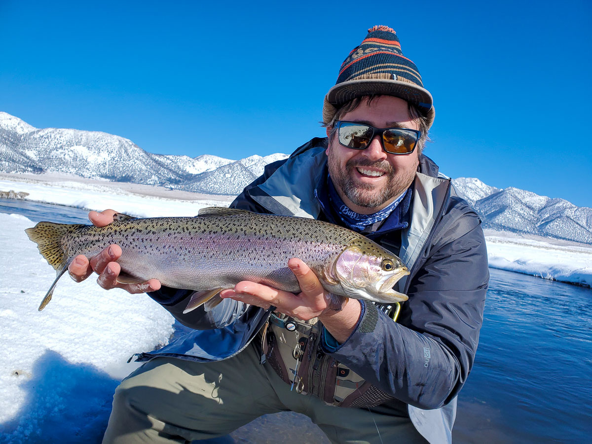 A masked fly fisherman holding a rainbow trout in spawning colors from the Upper Owens River.