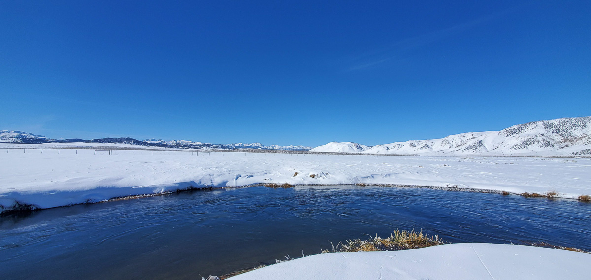 The Upper Owens River in the winter with snow all around.