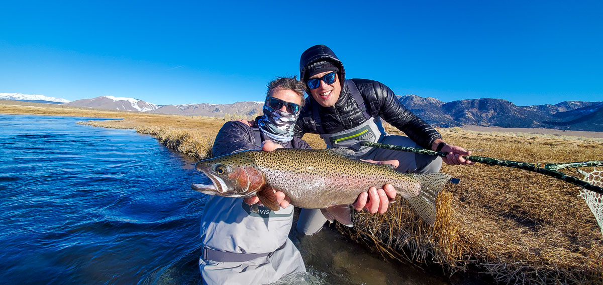 A pair of fly fisherman holding a rainbow trout in spawning colors from the Upper Owens River.