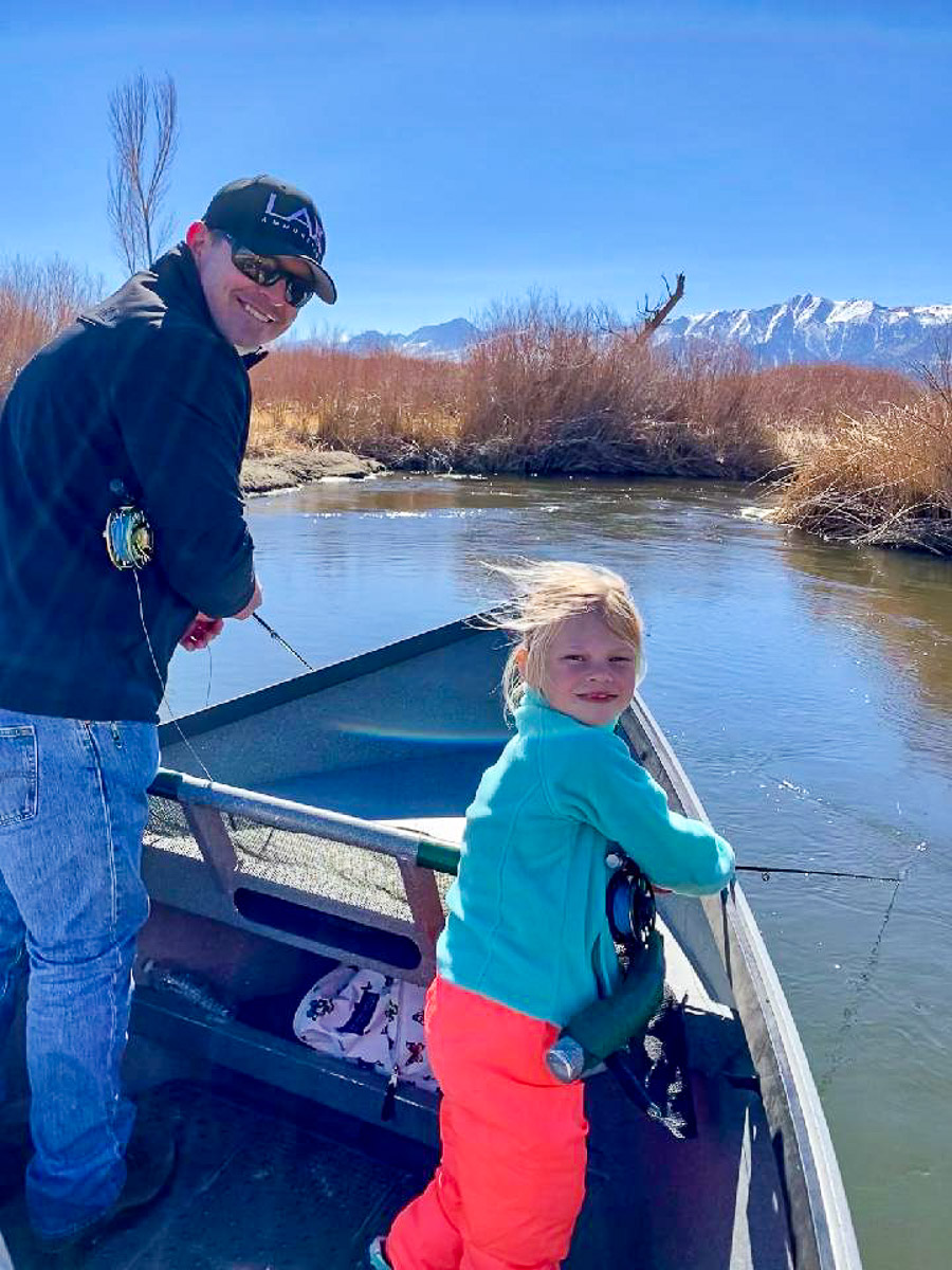 A father and daughter fly fishing from a drift boat on the Lower Owens River in Bishop.