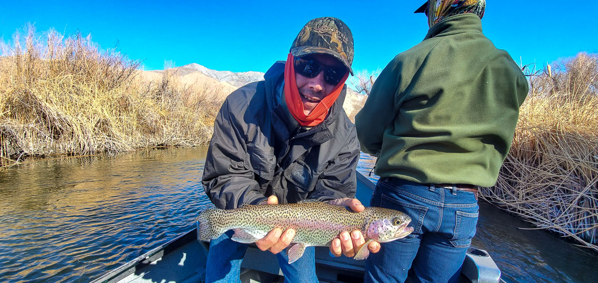 A fly fisherman in a drift boat holding a rainbow trout.