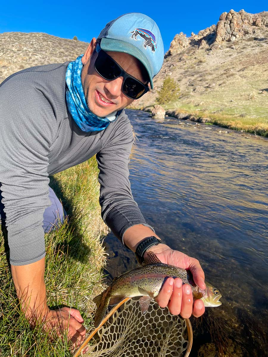 A fly fisherman with a light blue hat kneeling on a grassy river bank holding a rainbow trout in one hand.