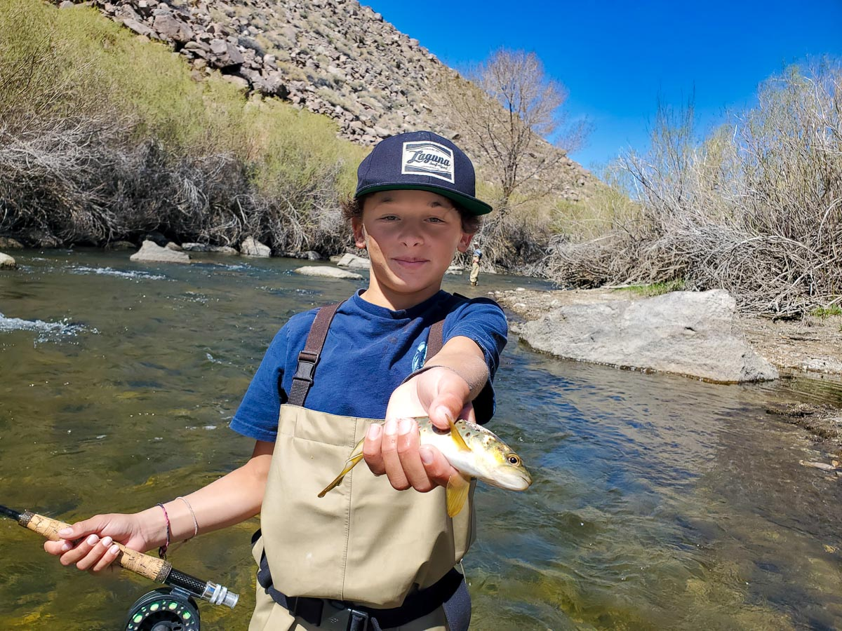 A fly fisherman youth holding a rainbow trout while standing in a river.