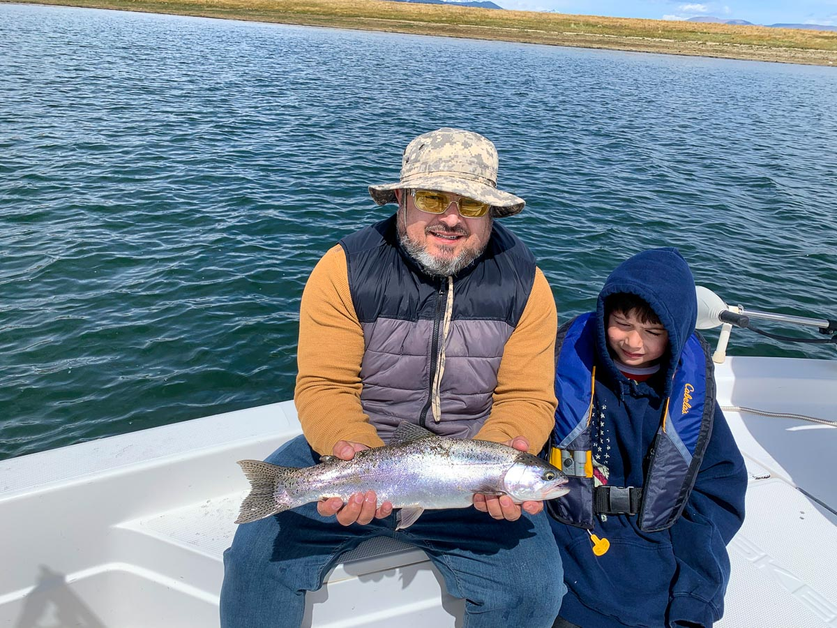 A fly fisherman holding a large rainbow trout in a boat on a lake with his young son by his side.