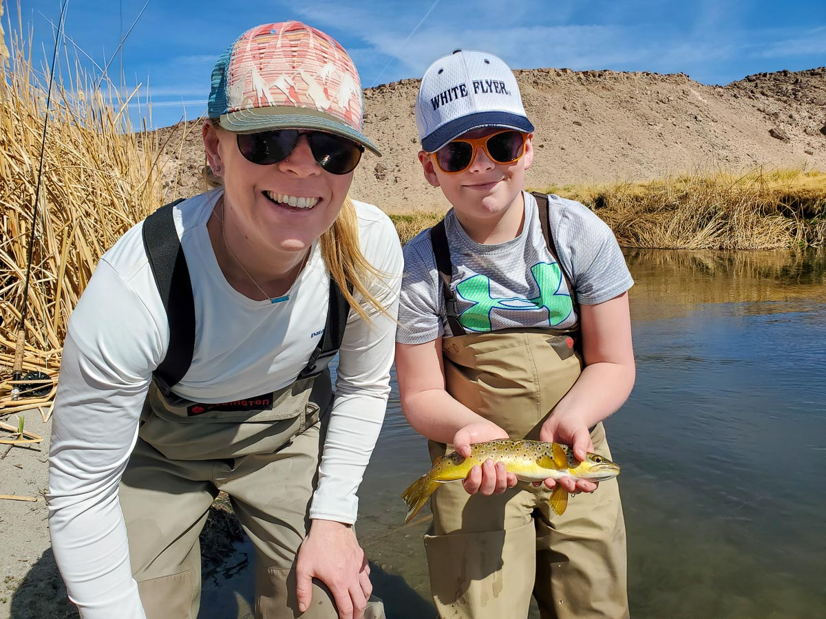 A fly fisherwoman and a young boy holding a brown trout from the Lower Owens River.