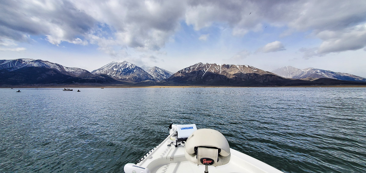 Looking out to the horizon from a boat on a lake in the eastern sierra with snowy mountains in the distance.