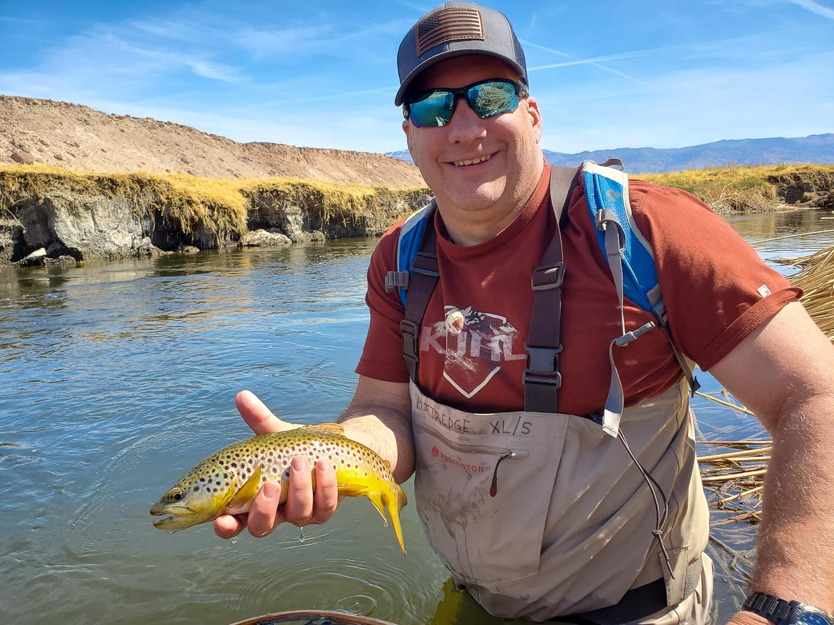 A fly fisherman standing in the river holding a brown trout.
