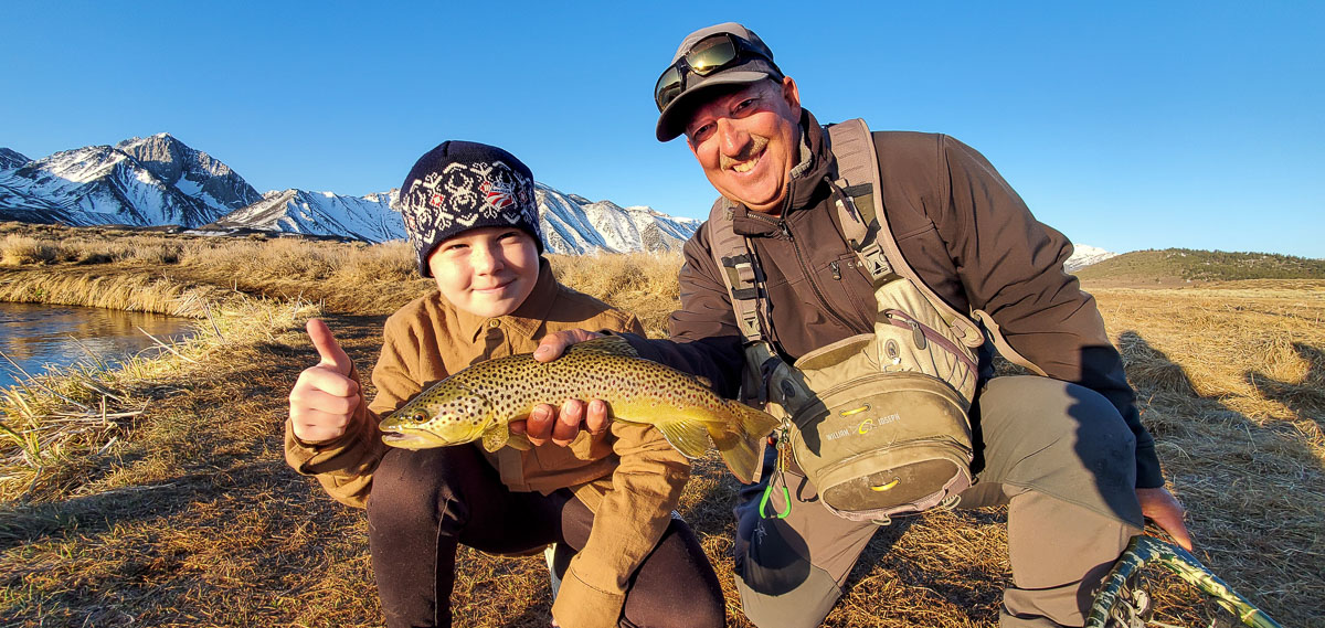 A young fly fisherman kid kneeling next to a man who is holding a brown trout with snowy mountains in the background.