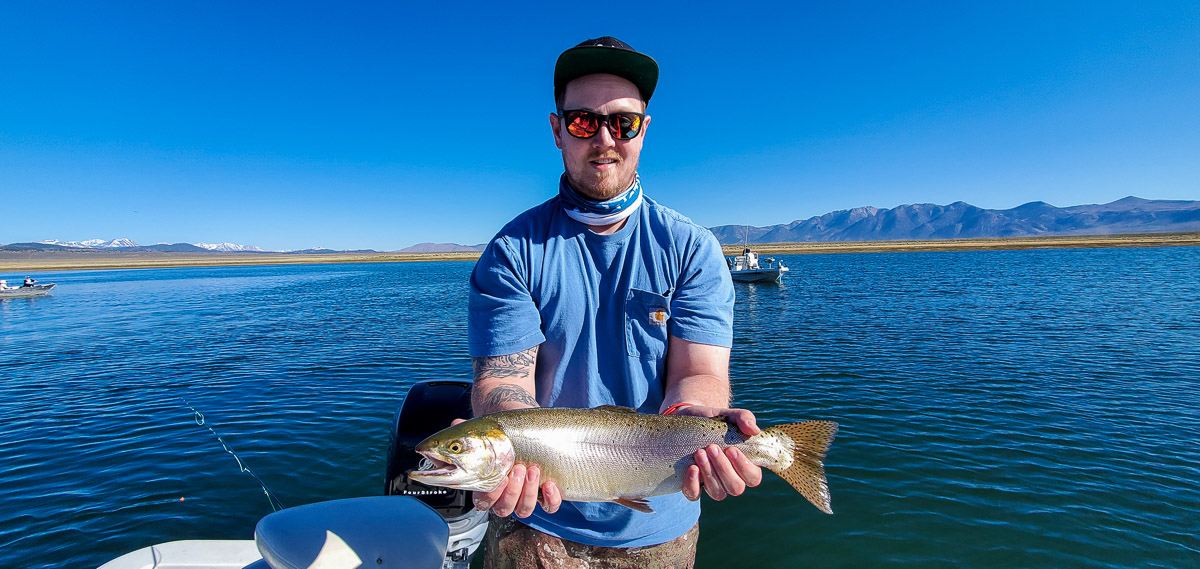 A smiling angler holding a cutthroat trout from Crowley Lake.