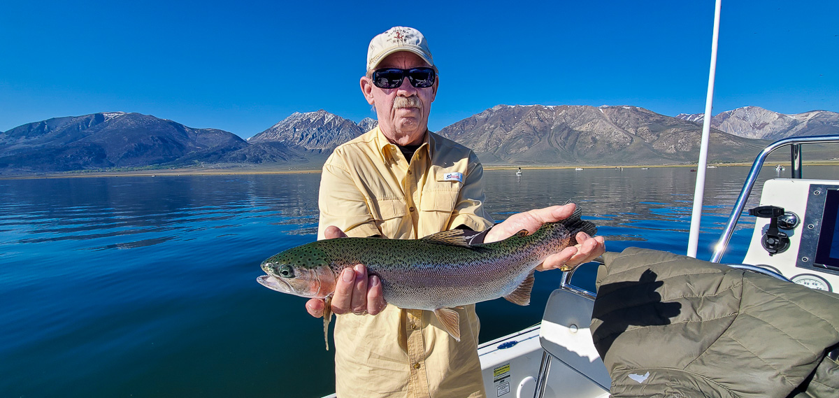 An elderly fly angler holding a massive rainbow trout on a lake while in a boat with mountains behind him.