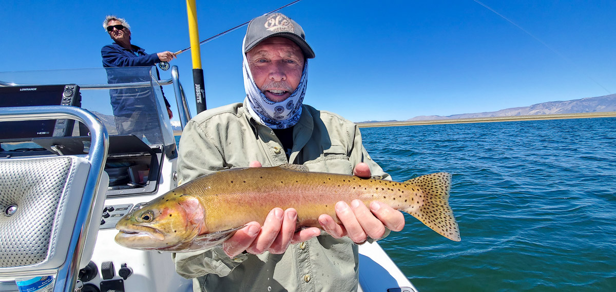 A fly fisherman with a grey hat holding a large cutthroat trout in a boat on a lake.