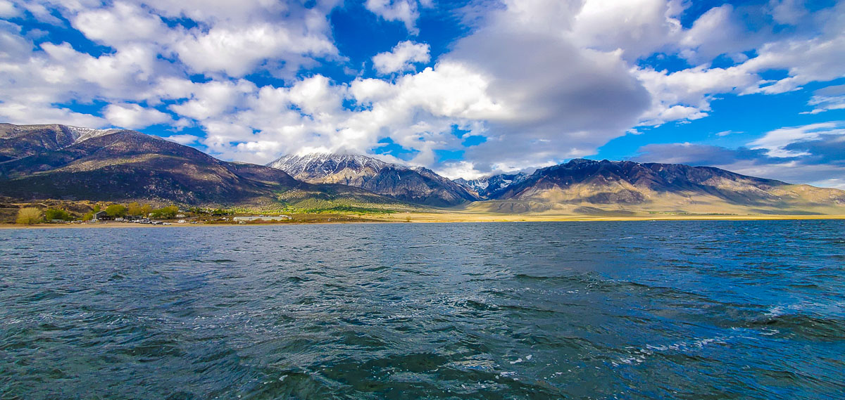 A mountain lake sitting against large mountains with snow on the tops and clouds above them.