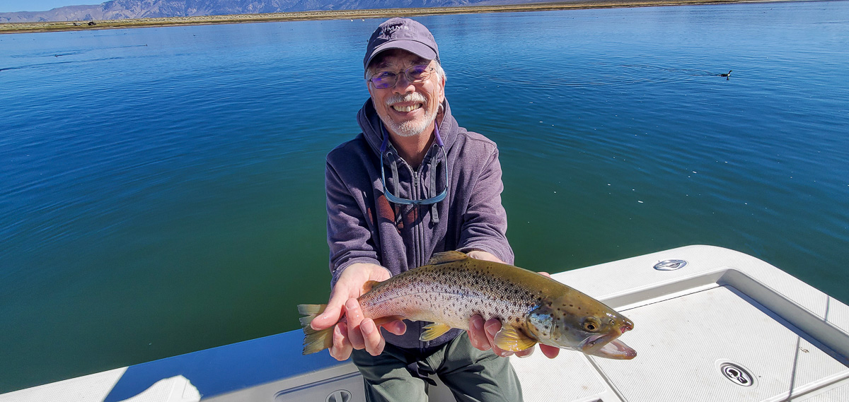 A fly fisherman with a purple hat holding a brown trout in a boat on a lake.