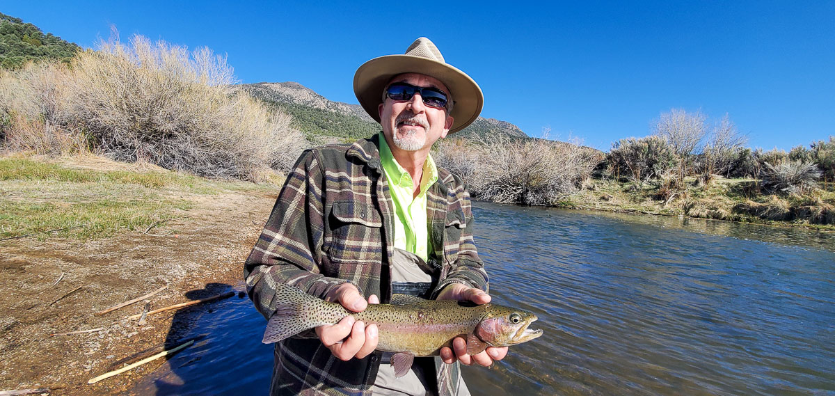 A fly fisherman with a wide-brimmed hat holding a rainbow trout while kneeling on the bank of a river