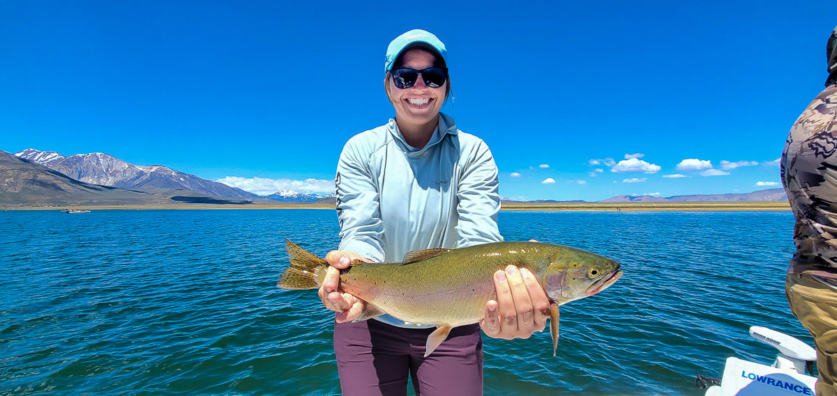 A female angler with a blue hat holding a large cutthroat trout on a lake.