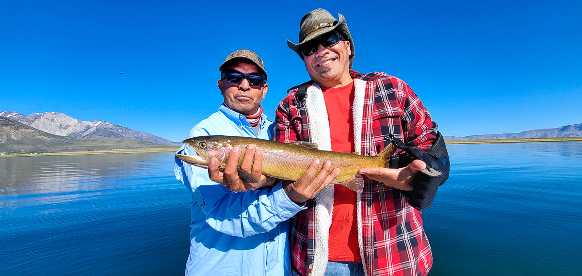 Two men holding a long cutthroat trout on a lake.