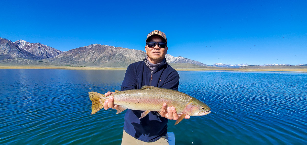 A man holding a large cutthroat trout on a lake.