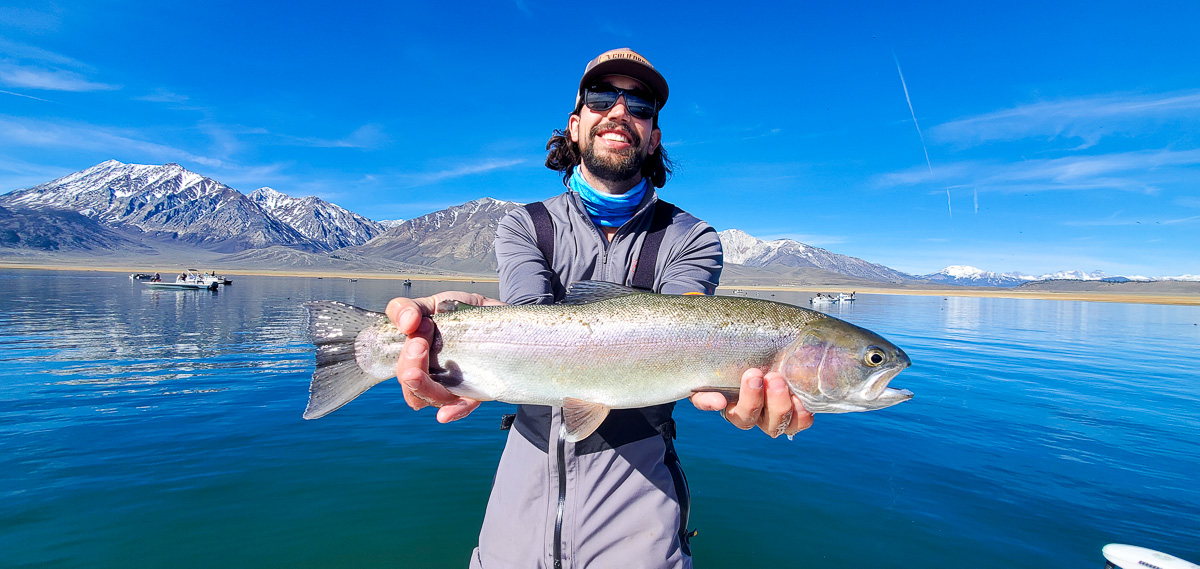 A bearded angler with a ball cap holding a rainbow trout in a boat on a glassy lake.